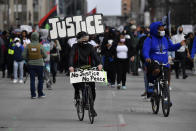 A bicyclist leads a group of protesters down Jefferson Street in Louisville, Ky., on the one year anniversary of the death of Breonna Taylor Saturday, March 13, 2021. (AP Photo/Timothy D. Easley)