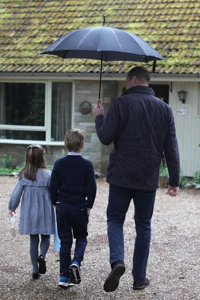 William holds an umbrella over George and Charlotte as they make a delivery. (The Duchess of Cambridge/PA Wire)