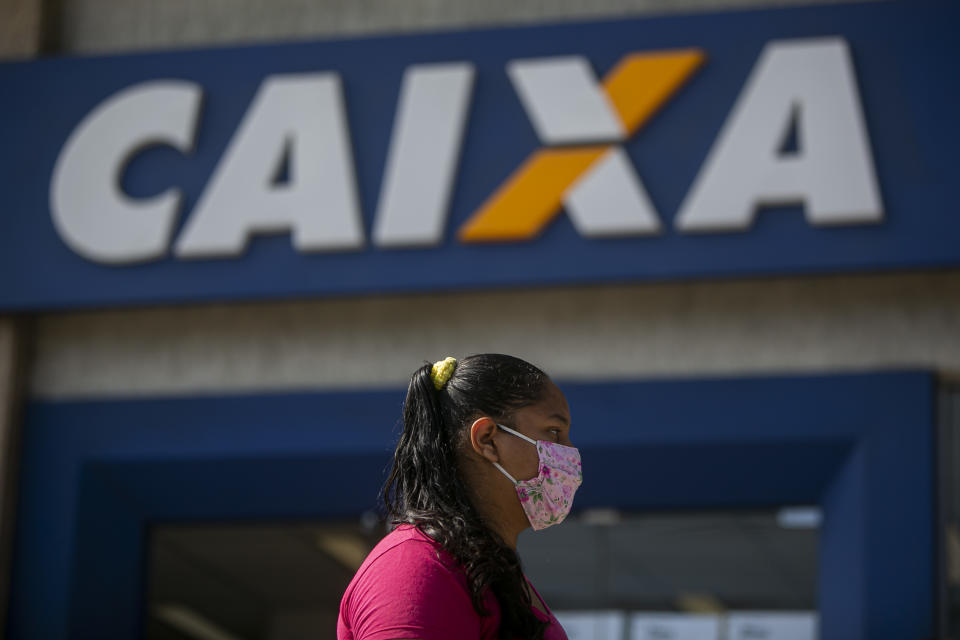 RIO DE JANEIRO, BRAZIL - MAY 18: A woman wearing a protective mask wait in line outside a Caixa Economica Federal bank branch in Campo Grande neighborhood to receive the second installment of the urgent government benefit amidst the coronavirus (COVID-19) pandemic on May 18, 2020 in Rio de Janeiro, Brazil. The benefit is directed at informal workers, small individual business owners, self-employed workers, and unemployed people under vulnerability, and it has been granted as part of the efforts to tackle the coronavirus (COVID-19) pandemic. According to city hall, Campo Grande is the neighborhood with the second highest number of deaths by coronavirus (COVID-19) in the city. (Photo by Bruna Prado/Getty Images)