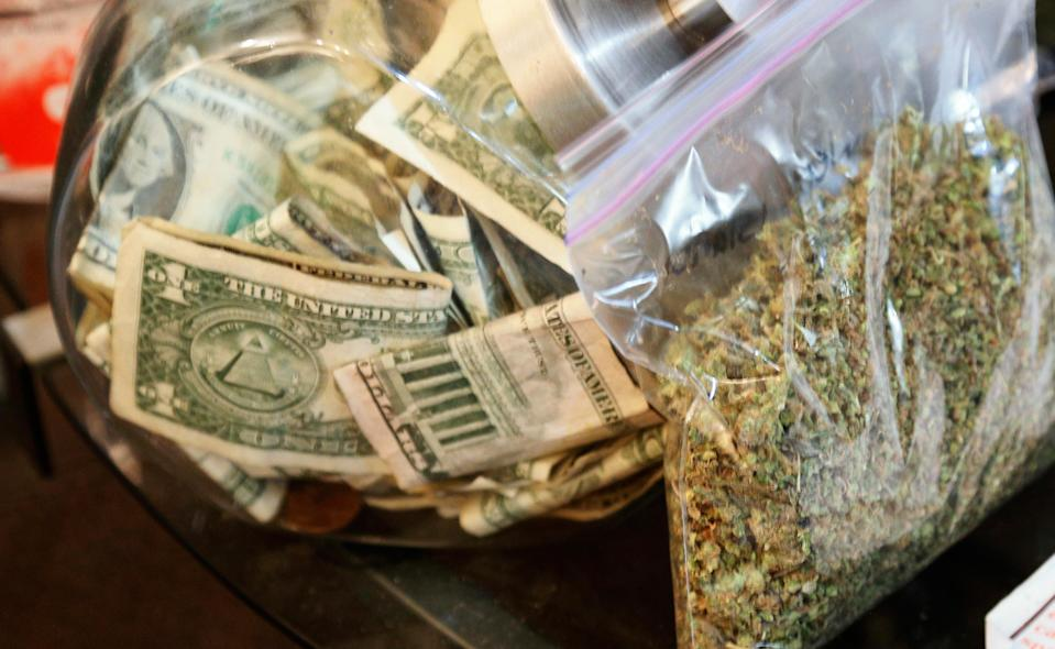 A bag of marijuana being prepared for sale sits next to a money jar at BotanaCare in Northglenn, Colorado, on December 31, 2013.