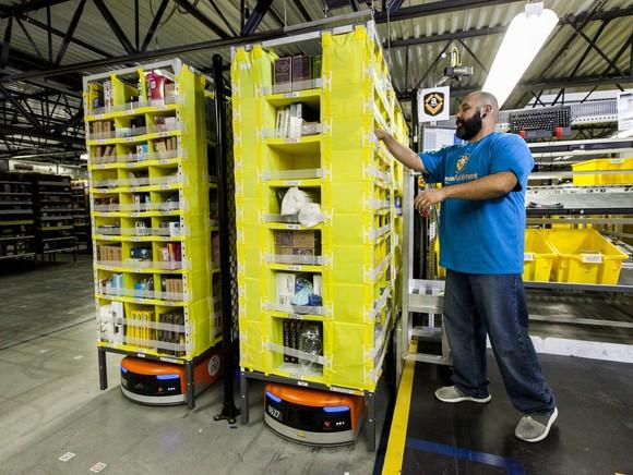 Amazon worker picking items in a fulfillment center.
