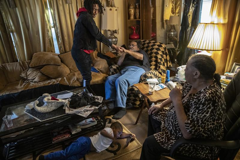 Taevion Rushing with his grandfather, Dennis Rushing, and grandmother, Linda, at home.