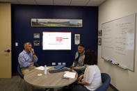 Ryan Smith, left, executive vice president of Ajinomoto Health and Nutrition North America, talks with colleagues during a company meeting at his office space in Itasca, Ill., Monday, June 7, 2021. Smith estimates 40% of the new headquarters design changed due to COVID. (AP Photo/Shafkat Anowar)