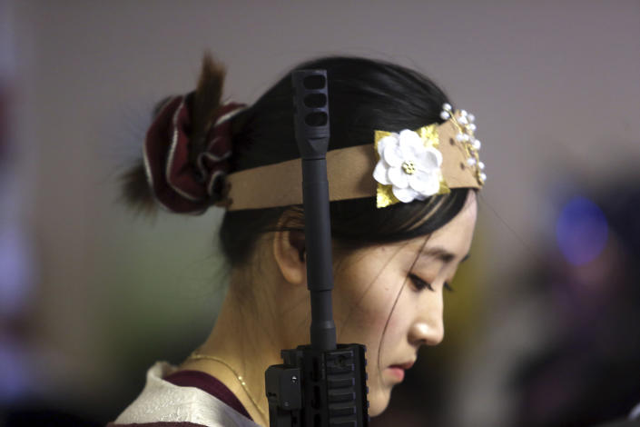 <p>A standing woman holds an unloaded weapon during services at the World Peace and Unification Sanctuary, Wednesday Feb. 28, 2018 in Newfoundland, Pa. (Photo: Jacqueline Larma/AP) </p>