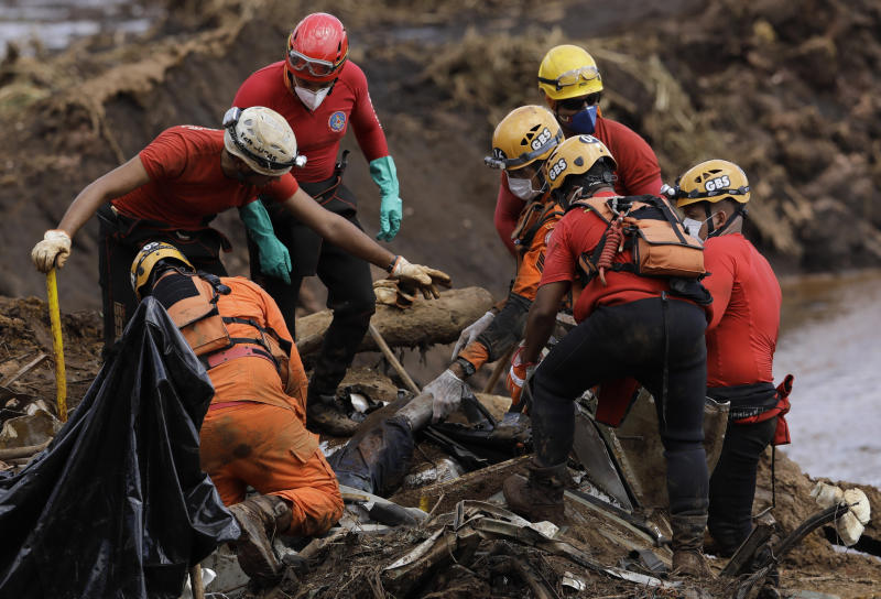 FILE - In this Jan. 28, 2019 file photo, firefighters pull a body from the mud days after a dam collapse in Brumadinho, Brazil. The wave of mud and debris that on Jan. 25, 2019 buried the equivalent of 300 soccer pitches and killed 270 people, continues to barrel over residents' minds, the local economy and the environment, one year later. (AP Photo/Leo Correa)