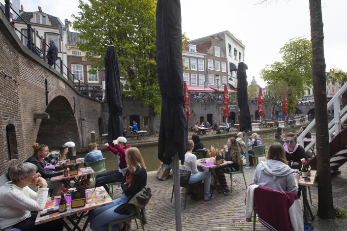 Dutch customers eager for their first drink of coffee or something stronger at a cafe terrace have flocked to outdoor seating as the Netherlands' lockdown eased in Utrecht, Wednesday, April 28, 2021. The Netherlands became the latest European country to begin cautiously relaxing its lockdown even as infection rates and intensive care occupancy remain stubbornly high. The Dutch follow Italy, Greece, France and other European nations in moving to reopen society and edge away from economically crippling lockdowns in the coming weeks. (AP Photo/Peter Dejong)