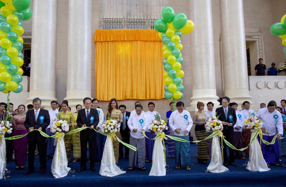 FILE - In this Dec. 9, 2015, file photo, senior government officials and foreign investors cut a ribbon during the opening ceremony of the Yangon Stock Exchange in Yangon, Myanmar. The military coup in Myanmar is unlikely to do the country's struggling economy any good at all. The country once considered a promising last frontier has languished as the pandemic added to its challenges. (AP Photo/Gemunu Amarasinghe, File)