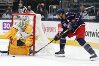 Nashville Predators' Juuse Saros, left, makes a save against Columbus Blue Jackets' Seth Jones during the second period of an NHL hockey game Monday, May 3, 2021, in Columbus, Ohio. (AP Photo/Jay LaPrete)
