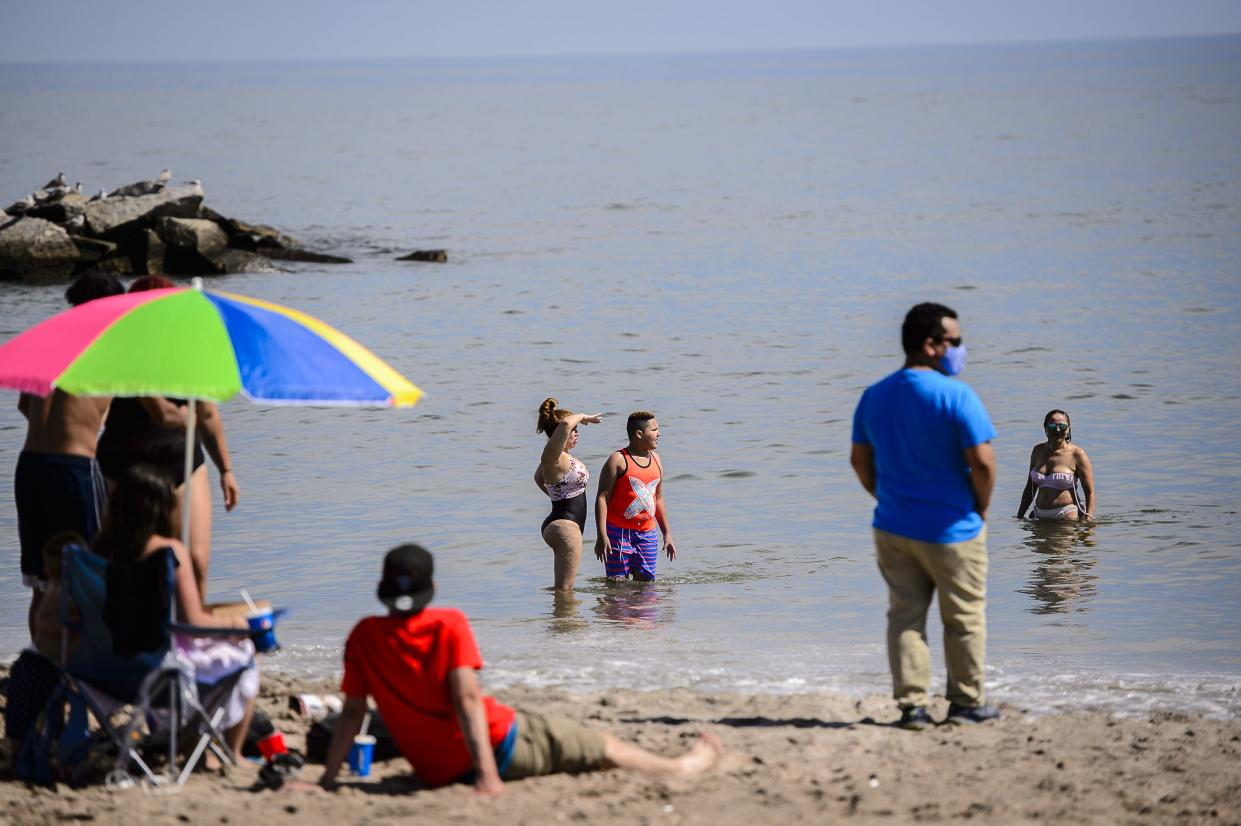 Families sit in the sand and play in the ocean at Coney Island Beach as swimming restrictions are eased across the city on July 1, 2020.
