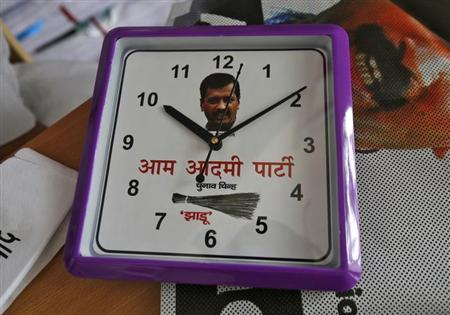 A wall clock carrying a portrait of Arvind Kejriwal, leader of the newly formed Aam Aadmi (Common Man) Party (AAP), and party symbol of a broom, lies on a table inside their party office in New Delhi October 1, 2013.REUTERS/Mansi Thapliyal