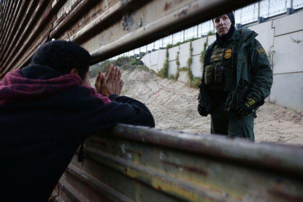 PHOTO: A Honduran migrant, left, talks with a Border Patrol agent as he tries to cross over the U.S. border wall to San Diego, California, from Playas in in Tijuana, Mexico, Dec. 15, 2018. (Moises Castillo/AP)