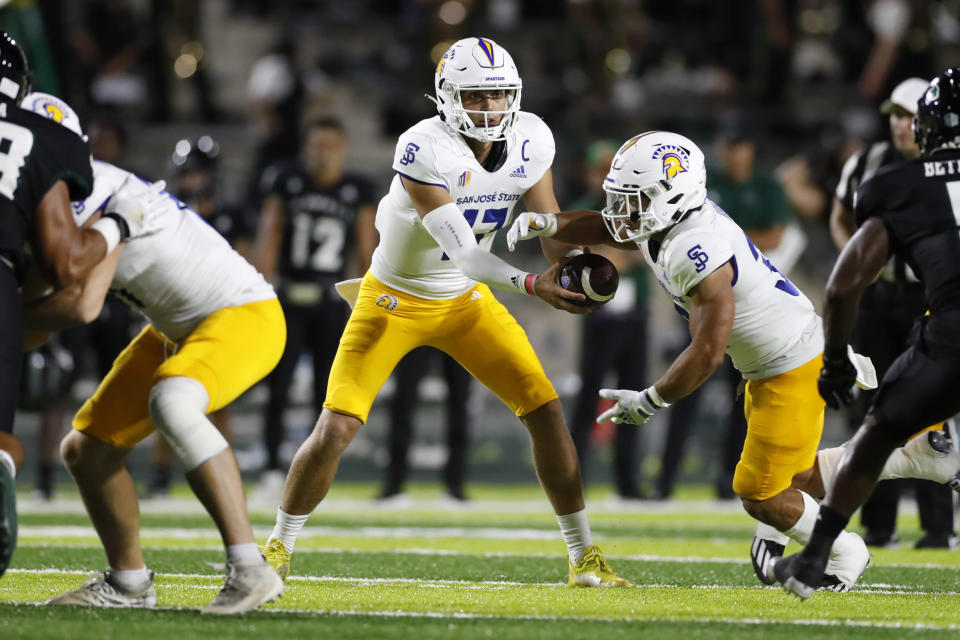 San Jose State corner back Zavion Reese (17) hands the ball to San Jose State running back Kairee Robinson (32) in the first half of a college football game against Hawaii, Saturday, Sept. 18, 2021, in Honolulu. (AP Photo/Marco Garcia)