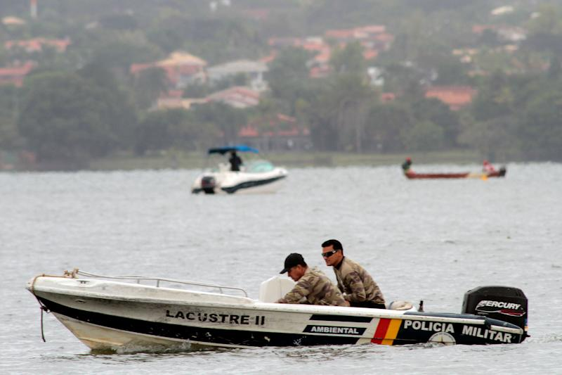 Police and divers conduct a search for bodies after a Sunday night boating accident left one child dead and at least seven other people missing, in Paranoa Lake, in Brasilia, Brazil, Monday May 23, 2011.  (AP Photo/Eraldo Peres)