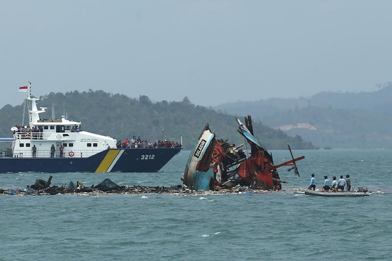 Indonesian navy crew (right) check one of seven fishing boats destroyed in Batam, Kepulauan Riau province on February 22, 2016