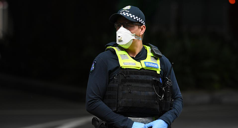 A Victorian Police officer wearing a face mask is seen outside of Crown Metropol Hotel in Melbourne
