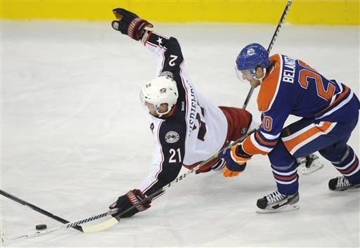 Columbus Blue Jackets' James Wisniewski, left, falls in front of Edmonton Oilers' Eric Belanger during the second period of an NHL hockey game Wednesday, March 14, 2012, in Edmonton, Alberta. (AP Photo/The Canadian Press, John Ulan)