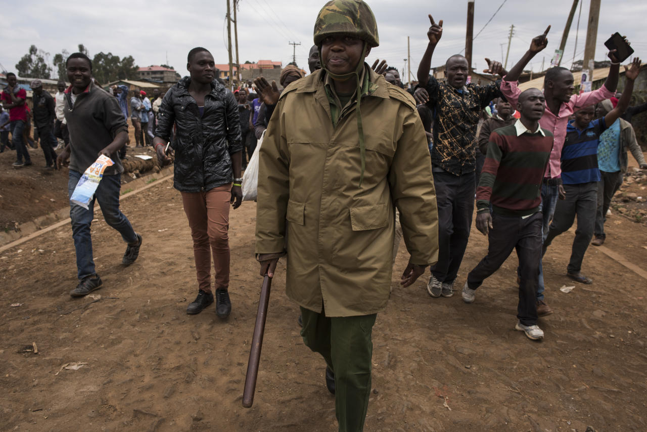 <p>Protestors yell for peace as they march behind a Kenyan police officer in the Kawangware slum, on August 10, 2017 in Nairobi, Kenya. Tensions remain high as rumors of election fraud surround the presidential election between incumbent president Uhuru Kenyatta and his rival Raila Odinga. (Photo: Andrew Renneisen/Getty Images) </p>