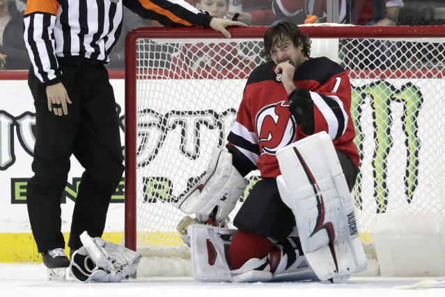 New Jersey Devils goaltender Keith Kinkaid (1) takes a moment after taking a stick to the mask during the second period of an NHL hockey game against the Carolina Hurricanes, Sunday, Feb. 10, 2019, in Newark, N.J. (AP Photo/Julio Cortez)