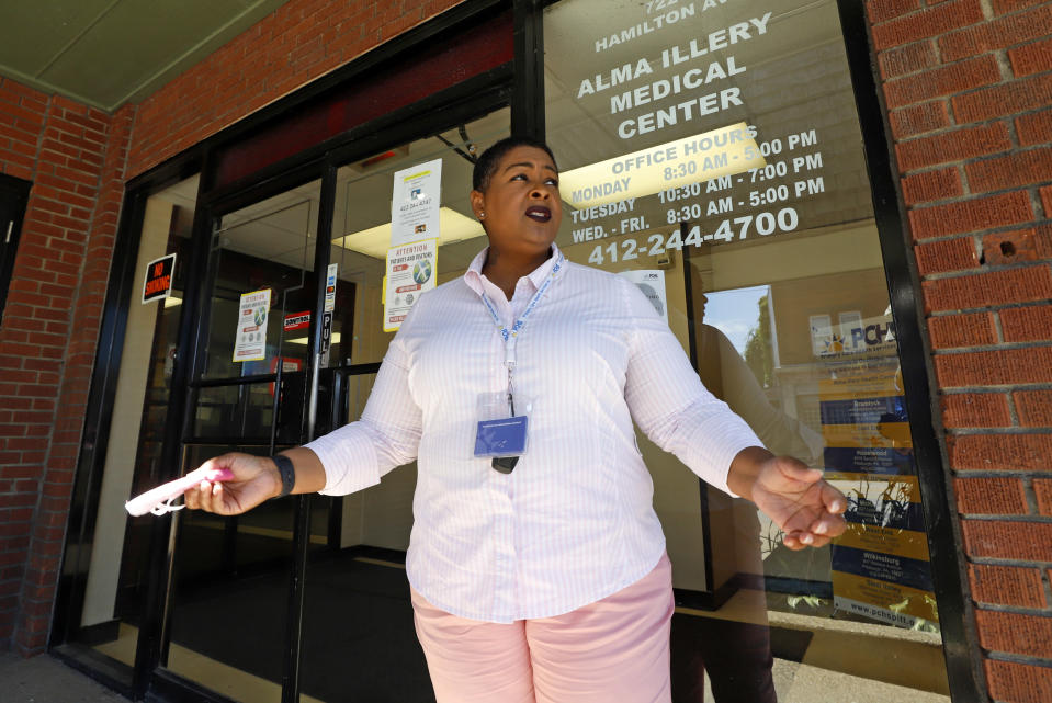 In this photo made on Monday, July 20, 2020, social worker Kiva A. Fisher-Green stands outside the Alma Illery Medical Center in the Homewood neighborhood of Pittsburgh. In March and April when Philadelphia and its surroundings became one of the nation's hot-spots for COVID-19 cases, Pittsburgh seemed at the time, to be under more control: the city racked up a fraction of the coronavirus cases as the other side of Pennsylvania. But by the beginning of July, officials in Pittsburgh's Allegheny County, began a cascading shutdown of bars, restaurants and gatherings due to an alarming spike in COVID-19 cases. (AP Photo/Gene J. Puskar)