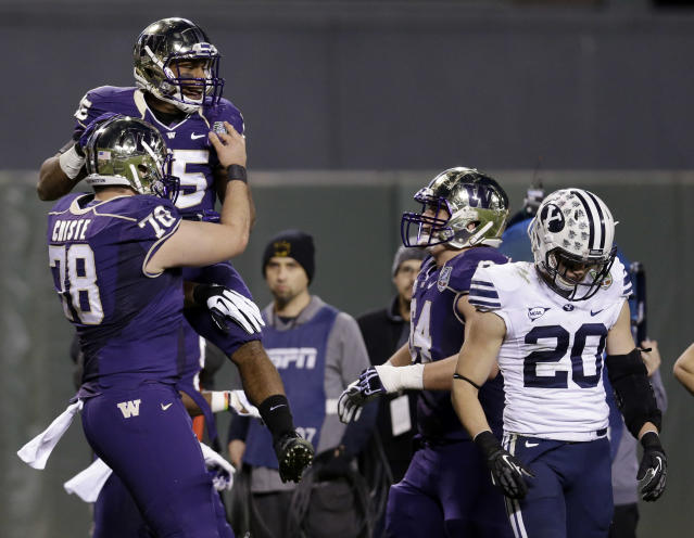 Washington running back Bishop Sankey is lifted by teammate Mike Criste after Sankey's rushing touchdown against BYU during first half of the Fight Hunger Bowl NCAA college football game, Friday, Dec. 27, 2013, in San Francisco. (AP Photo/Marcio Jose Sanchez)