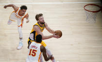Indiana Pacers Domantas Sabonis, center, shoots against Atlanta Hawks' Trae Young, left, and Clint Capela, right, during the first half of an NBA basketball game on Sunday, April 18, 2021, in Atlanta. (AP Photo/Brynn Anderson)