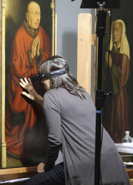 FILE - In this Oct. 11, 2012 file photo, a restorer inspects one of the 24 framed panels of the Altarpiece or Adoration of the Mystic Lamb, at the Fine Arts museum in Ghent, Belgium. If Rotterdam's stunning heist of Picasso, Monet and Matisse paintings last month focused attention on the murky world of art theft, Ghent's gothic Saint Bavo cathedral has been at the center of a crime that has bedeviled the art world for decades. The Just Judges panel of the Van Eyck brothers' multi-panel Gothic masterpiece hasn't been seen since 1934, when chief suspect Arsene Goedertier suffered a stroke at a political rally close to Ghent and died after murmuring possibe clues to the crime to a  confidant. (AP Photo/Yves Logghe, File)