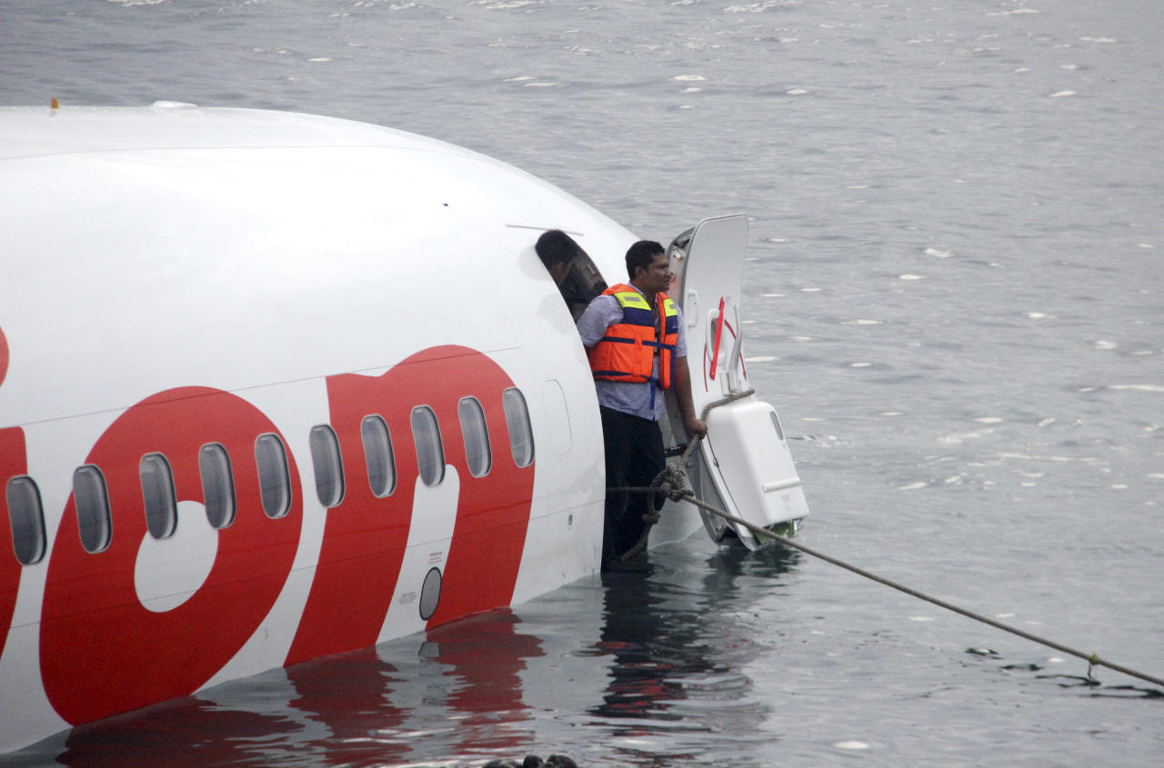 In this photo released by Indonesian Police, a rescue worker stands at the doorway of a crashed Lion Air plane on the water near the airport in Bali, Indonesia on Saturday, April 13, 2013. The plane carrying more than 100 passengers and crew overshot a runway on the Indonesian resort island of Bali on Saturday and crashed into the sea, injuring nearly two dozen people, officials said. (AP Photo/Indonesian Police)