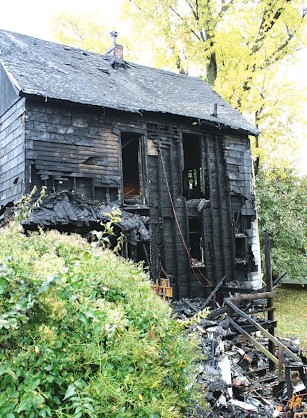 In this Oct. 31, 2013 photo provided by the Louisiana Press-Journal is the back of a home following a fire in Louisiana, Mo. The family of 3-year-old Riley Miller who was killed in the fire says it is outraged after police used a stun gun on the boy's stepfather as he tried to run back in and save the child. (AP Photo/Courtesy Louisiana Press-Journal, Tim Schmidt) MANDATORY CREDIT
