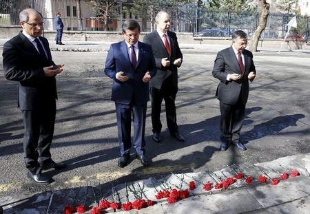 Turkish PM Davutoglu prays as he visits the site of Wednesday's suicide bomb attack in Ankara