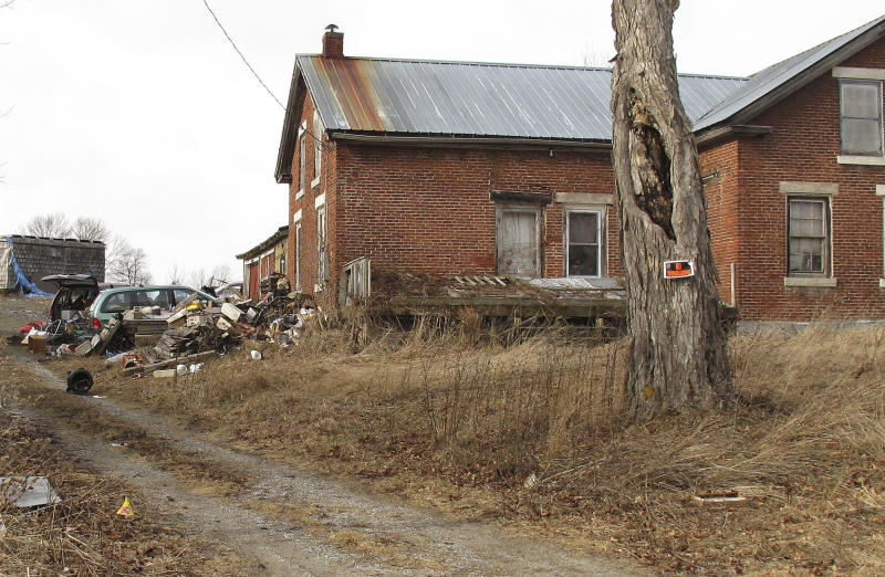Cars, debris and outbuildings rest on the property where an eccentric man known simply as Radkin lived in Alburgh, Vt., Friday, Feb. 1, 2013.  It took months for anyone to discover that Radkin had died in an accident on his land. But four people – Mark Mumley, Shawn Farrell, Ricky Benjamin and Jennifer Jarvis – are facing charges for stealing more than $200,000 in gold coins and other items from the property.  (AP Photo/Wilson Ring)