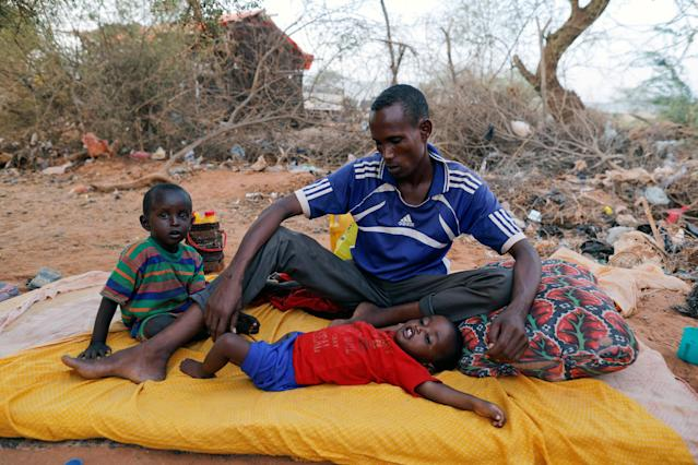 FILE PHOTO: A Somali internally displaced man from drought-hit area sits with his children as he waits for help in Dollow, Somalia April 3, 2017. REUTERS/Zohra Bensemra/File photo