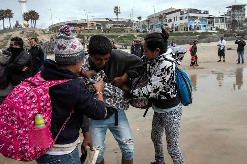 A Central American migrant carrying a child is helped after being sprayed by US Border Patrol agents while trying to cross the US-Mexico border (AFP Photo/Guillermo Arias)