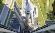 In this image released by NASA, a United Launch Alliance Atlas V rocket with the Lucy spacecraft aboard is rolled out of the Vertical Integration Facility to the launch pad at Space Launch Complex 41, Thursday, Oct. 14, 2021, in Cape Canaveral, Fla. The robotic trailblazer named Lucy is slated to blast off on Saturday on a 12-year cruise to unexplored swarms of asteroids out near Jupiter. (Bill Ingalls/NASA via AP)