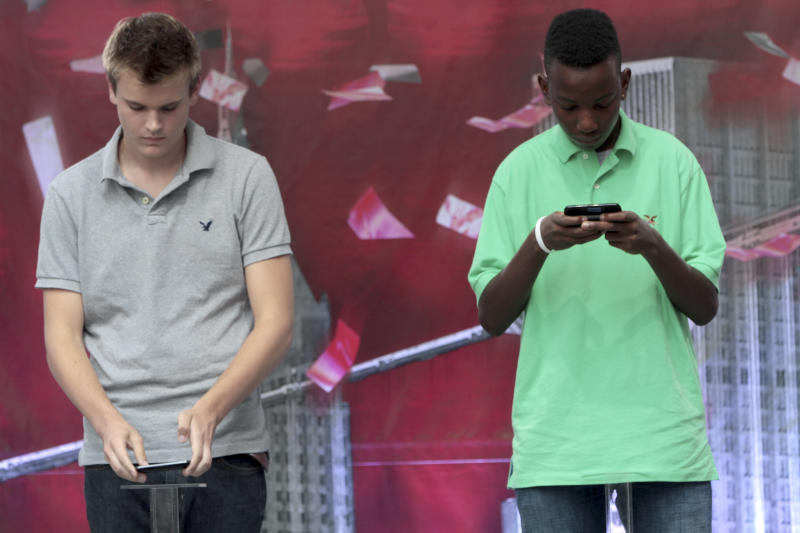 Austin Wierschke, left, of Rhinelander, Wi., places his phone on a podium after finishing texting ahead of  Kent Augustine, Jamaica, N.Y.,  during the final round of the 2012 LG U.S. National Texting Championship, Wednesday, Aug. 8, 2012 in New York.  (AP Photo/Mary Altaffer)