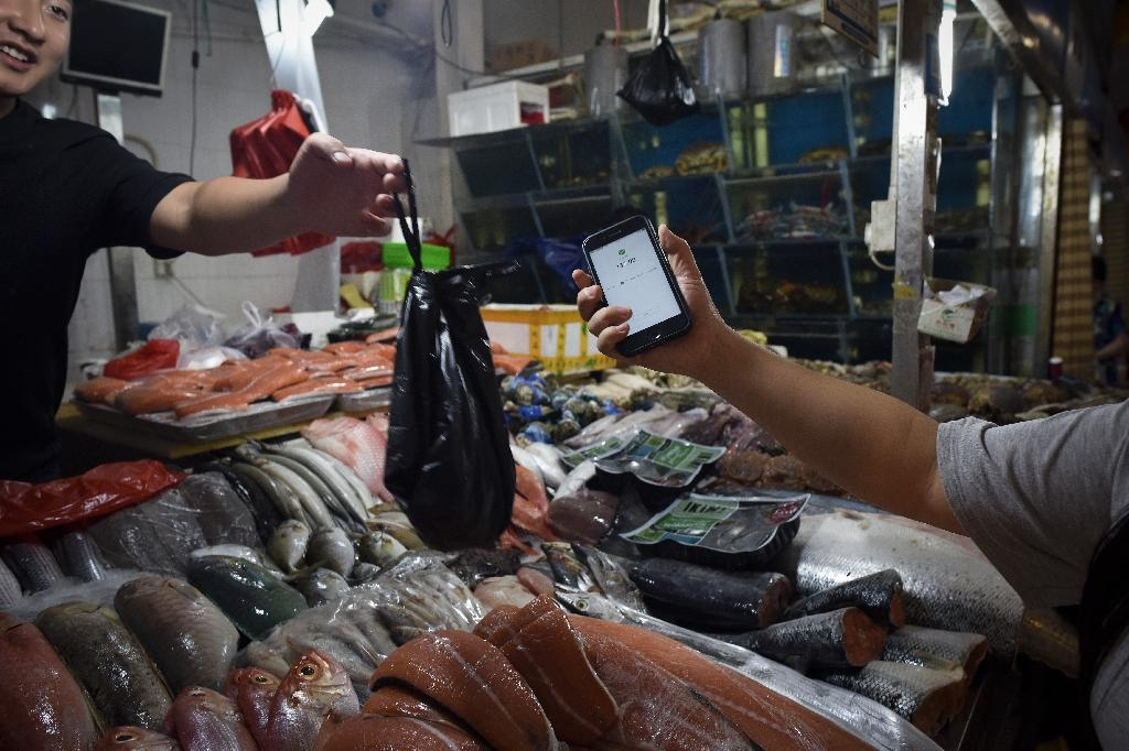 This photo taken on June 27, 2017 shows a man making purchases through his smartphone at a seafood booth at a market in Beijing (AFP Photo/WANG ZHAO)