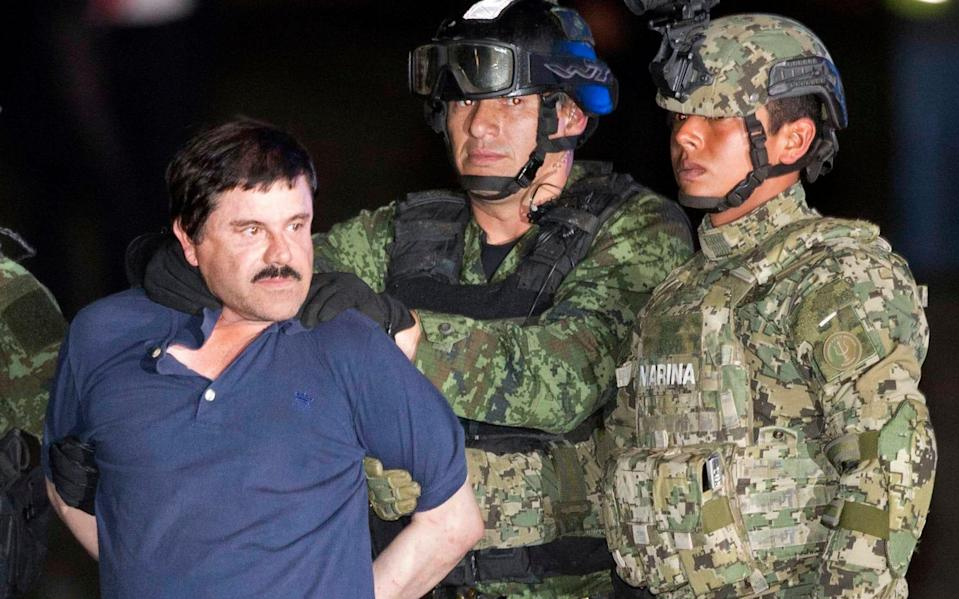 """Joaquin """"El Chapo"""" Guzman is made to face the press as he's escorted to a helicopter in handcuffs by soldiers and marines at a federal hangar in Mexico City - Eduardo Verdugo/AP"""