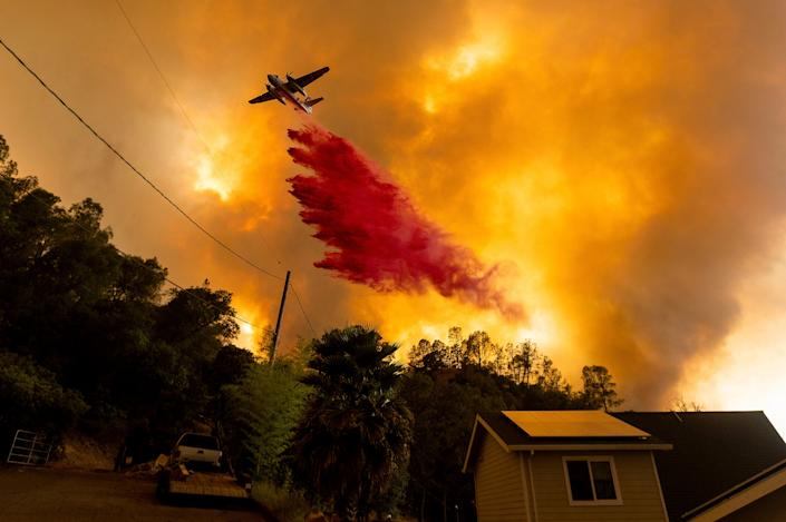 An air tanker drops retardant as the LNU Lightning Complex fires tear through the Spanish Flat community in unincorporated Napa County, Calif., Tuesday, Aug. 18, 2020. Fire crews across the region scrambled to contain dozens of wildfires sparked by lightning strikes as a statewide heat wave continues.