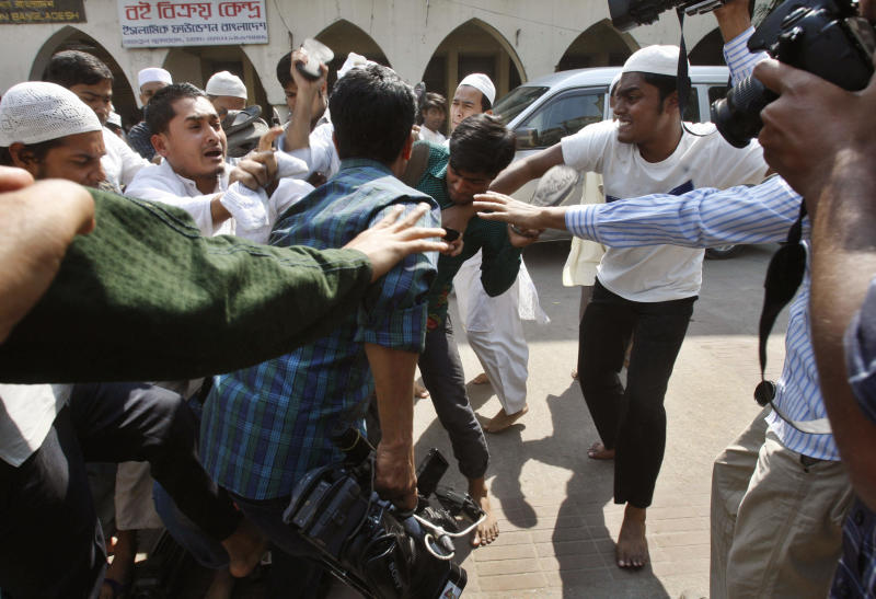 Muslim activists attack television crew members after their widespread coverage calling on the International Crimes Tribunal (ICT) to impose death sentences to people accused of mass scale human rights abuses during Bangladesh's 1971 independence war, during a protest in Dhaka, Bangladesh, Friday, Feb. 22, 2013. Police fired rubber bullets and tear gas Friday to disperse thousands of rampaging protesters from Islamic parties, leaving two people killed and dozens injured, police and witnesses said. The nationwide protests were held separately by Jamaat-e-Islami, the country's largest Islamic party and an alliance of 12 other smaller Islamic groups to denounce the war crimes trial of its top leaders. (AP Photo/Pavel Rahman)