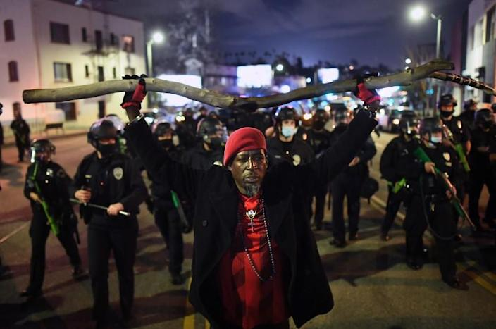 LOS ANGELES CALIFORNIA MARCH 25, 2021-A protestor is pushed back by LAPD officers on Sunset Blvd. as authorities evict the homeless from Echo Park Thursday. (Wally Skalij/Los Angeles Times)