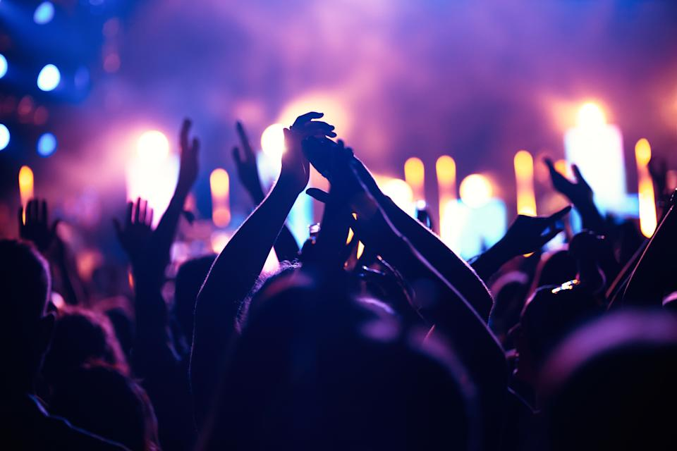 Happy cheering crowd with hands in air at music festival