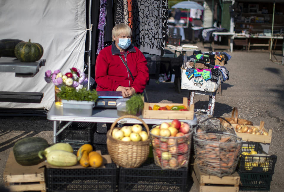 A vegetable vendor wearing a face mask to protect against coronavirus, waits for customers at the bazaar in the small town of Ignalina, some 110km (68.3 miles) north of the capital Vilnius, Lithuania, Saturday, Sept. 26, 2020. (AP Photo/Mindaugas Kulbis)