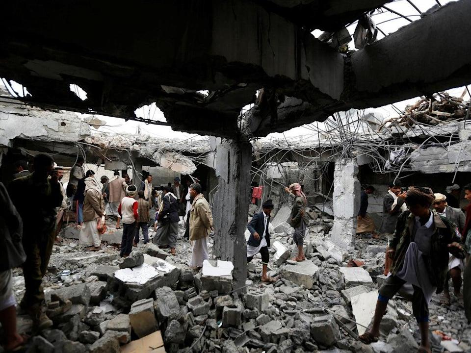 People gather at a building destroyed by Saudi-led air strikes in the northwestern city of Amran, Yemen (Reuters)
