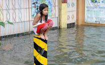 A soaking wet child sits on a post on a flooded street in suburban Manila on August 8, 2012. Twenty people have died from this week's rains in Manila and nearby provinces, according to authorities