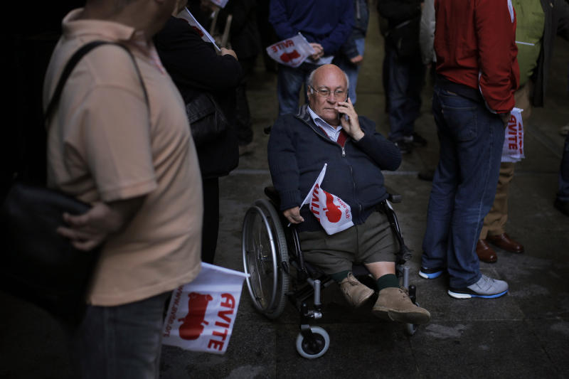"""Spaniards born with severe defects protest outside Court holding flags reading """"Avite"""" (Spanish Thalidomide's Victim Association) as they wait for the trial against German company Gruenenthal Group to start in Madrid, Spain, Monday, Oct. 14, 2013. Spaniards born with severe defects after their mothers used the drug Thalidomide during their pregnancies are suing its producer, the German company Gruenenthal Group. The Monday trial will last one day and a ruling is expected within a month. Many of the children of the mothers who took the drug, a sedative prescribed between 1950 and 1960 to combat morning sickness, were born with abnormally short limbs and in some cases without any arms, legs or hips. Gruenenthal, who withdrew Thalidomide in 1961, has refused to accept liability, but last year it apologised to victims. (AP Photo/Andres Kudacki)"""