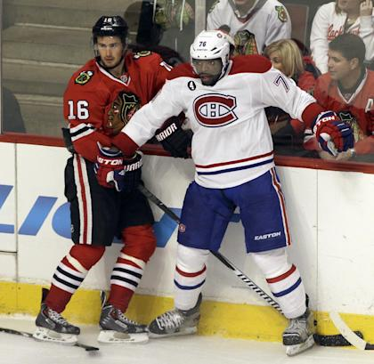 In this photo taken on Dec. 5, 2014, Montreal Canadiens defenseman P.K. Subban (76) and Chicago Blackhawks center Marcus Kruger (16) watch the puck during the third period of an NHL hockey game in Chicago. Subban's outgoing, over-the-top personality is matched only by his unbridled ability, which have made him a fan-favorite in Montreal, the NHL's highest paid blue-liner and among the league's most talked-about players. (AP Photo/Nam Y. Huh)