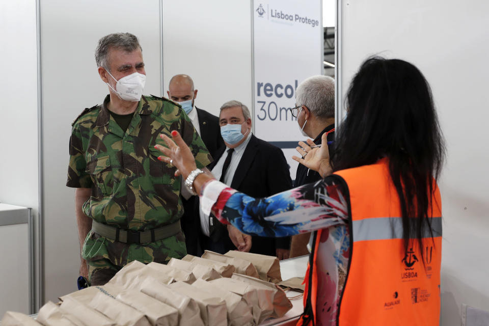 A volunteer at a vaccination center greets Rear Admiral Henrique Gouveia e Melo as he arrives at the center in Lisbon, Saturday, Sept. 11, 2021. As Portugal nears its goal of fully vaccinating 85% of the population against COVID-19 in nine months, other countries want to know how it was able to accomplish the feat. A lot of the credit is going to Gouveia e Melo. (AP Photo/Armando Franca)