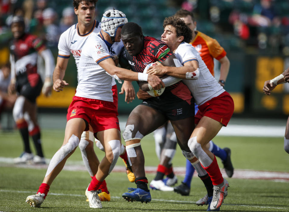 Kenya's Alvin Otieno, center, is tackled by Spain's Alberto Carmona, left, and Josep Serres during an HSBC Canada Sevens rugby match in Edmonton, Alberta, Saturday, Sept. 25, 2021. (Jeff McIntosh/The Canadian Press)