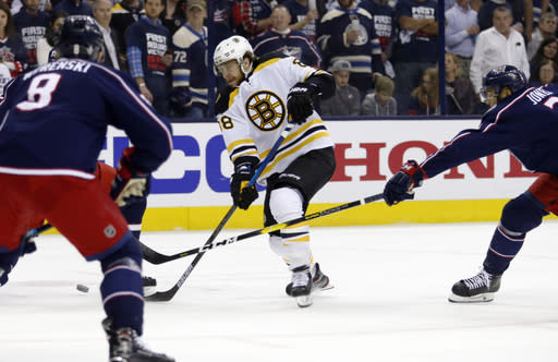 Boston Bruins forward David Pastrnak, center, of the Czech Republic, passes between Columbus Blue Jackets defenseman Zach Werenski, left, and defenseman Seth Jones during the first period of Game 4 of an NHL hockey second-round playoff series in Columbus, Ohio, Thursday, May 2, 2019. (AP Photo/Paul Vernon)