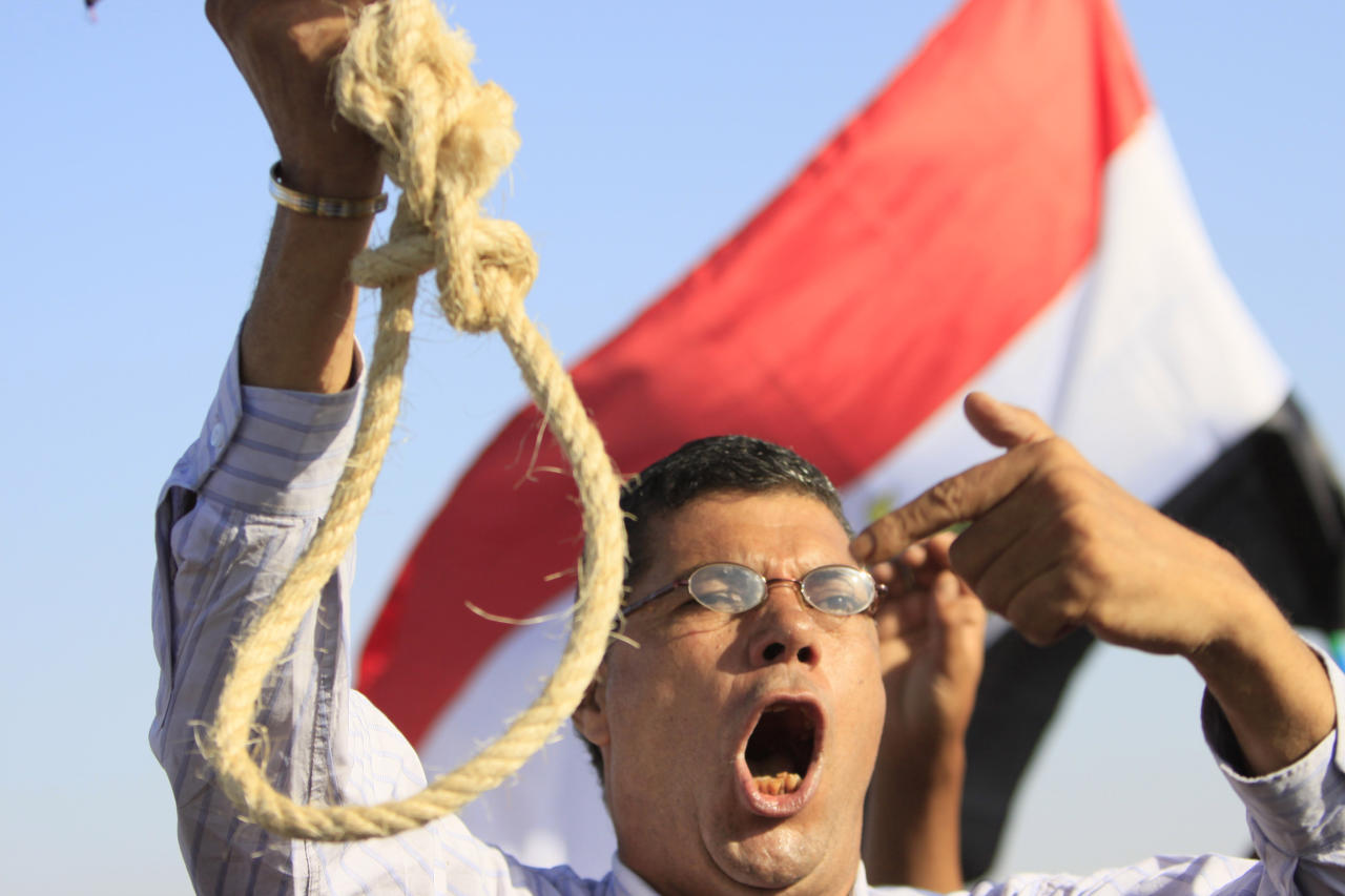 An Egyptian anti-Mubarak protester flashes a noose during a protest outside the police academy in Cairo, Egypt, Wednesday, Aug. 3, 2011. Ousted President Hosni Mubarak, together with his two sons Alaa and Gamal, his security chief Habib el-Adly and six top police officers, face trial, on charges of corruption and ordering the killing of protesters during the uprising that ousted him. (AP Photo/Amr Nabil)