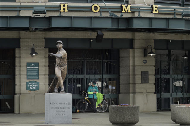 Al Jackson, a die-hard Seattle Mariners fan and 11-year season ticket holder, leans against the gate at the home plate entrance near the Ken Griffey Jr. statue at T-Mobile Park in Seattle, March 26, 2020, around the time when the Mariners' Opening Day baseball game against the visiting Texas Rangers would have started. (AP Photo/Ted S. Warren)